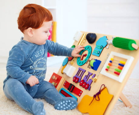 Toddler looking at a toy clock