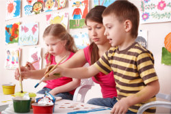 The teacher and her students are paiting happily